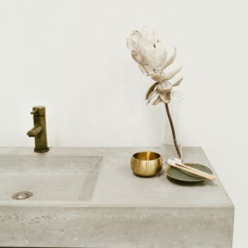 Cream marble bathroom basin and bench detail supported by brown metal beam