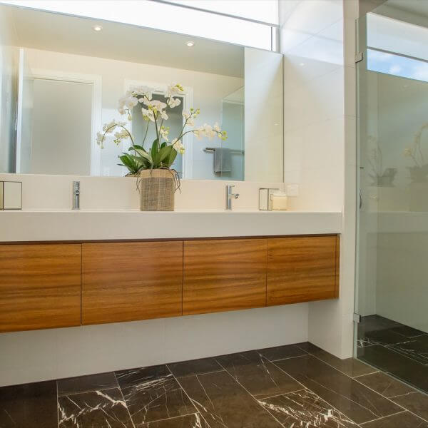 A beautiful modern bathroom. Elegant with Modern wash basins, Cream Bathroom with Marble Floor and wooden shelves